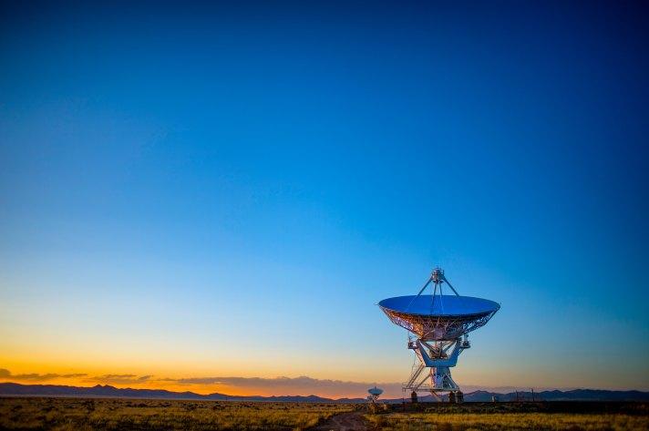 A photo of a radar dish pointed upward at sunrise